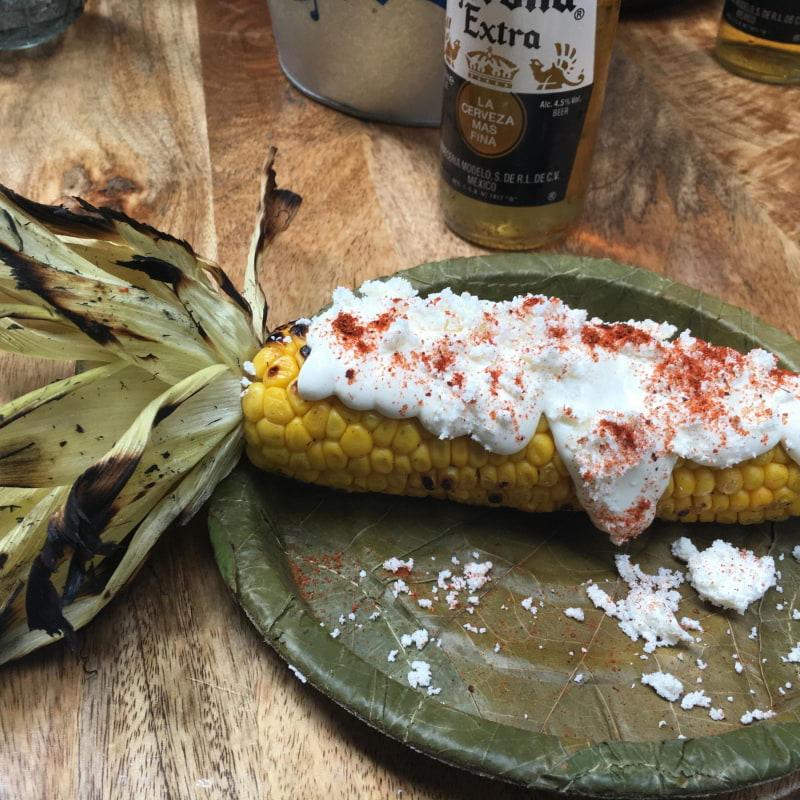 Elote! Smörkokt och grillad majskolv med majonnäs, som toppas med ost och granulerad chili. – Bild från Munchies Streetfood av Marie F.