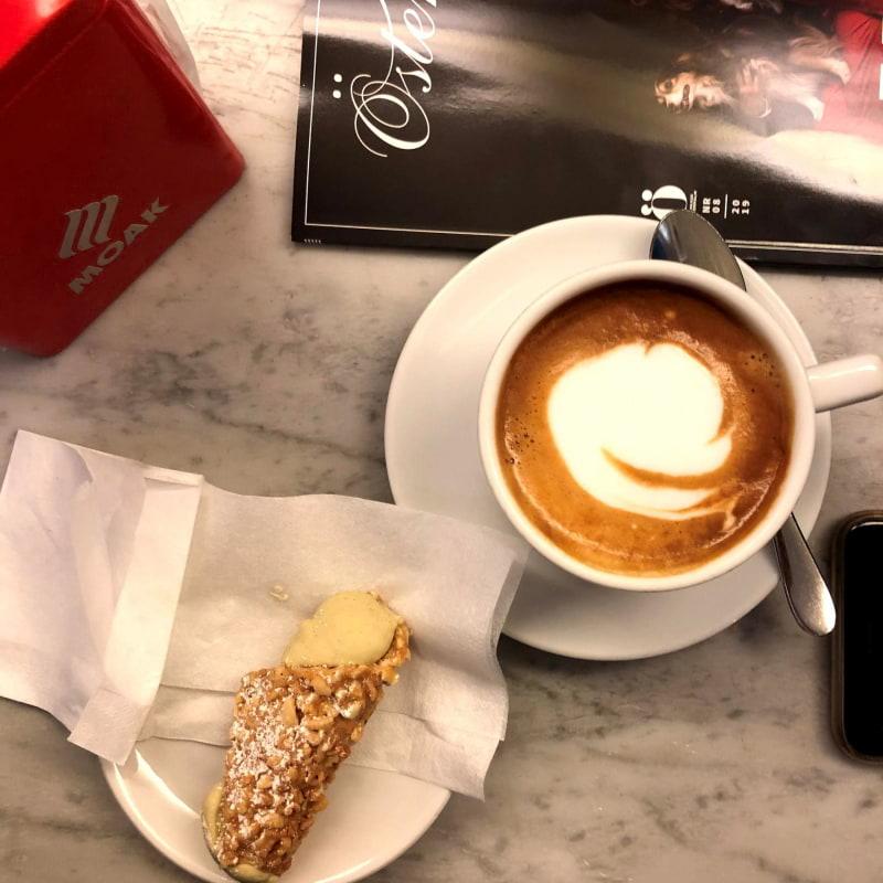Cappuccino med klassiskt Italienskt kondis bit – Bild från Sempre Espresso Bar av Madiha S.